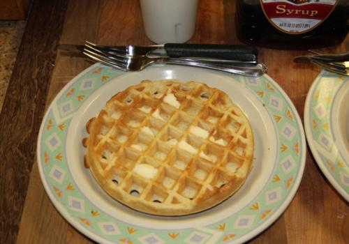 Plated waffle with butter waiting to be served
